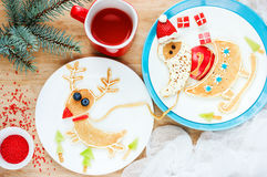 Funny pancakes Santa Claus and reindeer ride in a sleigh. Creative idea for Christmas breakfast , healthy and festive baby meal Stock Photography