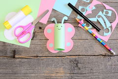 Funny paper butterfly, scissors, marker, glue stick, colored paper sheets and scraps, pencil on old wooden table Royalty Free Stock Photo