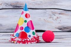 Funny party clown costume. Clowns fancy hat and red nose on wooden background. Holiday party accessories royalty free stock images