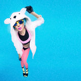 Funny party girl in hoodie bear on a blue background. Bright win Royalty Free Stock Images