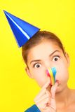 Funny party woman. In blue on yellow background. Beautiful mixed race / asian caucasian model with party hat blowing a party blower at the camera Stock Image