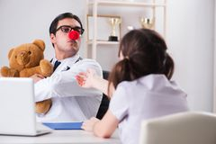 The funny pediatrician with little girl at regular check-up Royalty Free Stock Photos