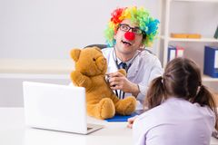The funny pediatrician with little girl at regular check-up Royalty Free Stock Photo