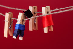 Funny peg characters and clothesline. Man in suit, woman red dress. wooden clothespins macro view, shallow depth of Royalty Free Stock Photos