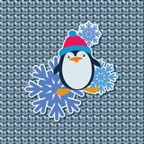 Funny penguin in a red hat and snowflakes. Sticker, emblem on gray knitted background. Design for printing on fabrics, paper, gift wraps Royalty Free Stock Photos