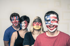 Funny people with painted flags on faces. Group of funny people with painted flags on their faces stock photo