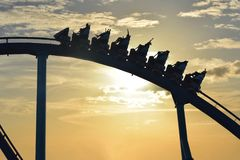 Funny people riding Mako Rollercoaster at Seaworld on sunset background. Orlando, Florida. September 21, 2018. Funny people riding Mako Rollercoaster at stock photography