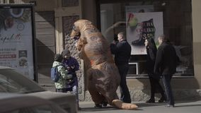 Funny person in dinosaur costume messing with pedestrians on city sidewalk. Funny person in dinosaur costume jokingly messing with pedestrians on crowded city stock footage