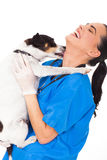 Dog licking vet. Funny pet dog licking vet nurse's neck on white background royalty free stock images