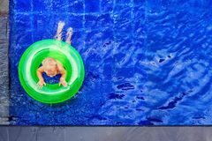Happy child have fun on inflatable ring in swimming pool Stock Images