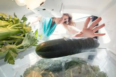 Healthy diet: A hand in an open refrigerator full of greens. A funny photo of healthy diet: A hand in an open refrigerator full of greens. A view from inside Stock Photography