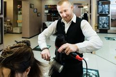 Funny photo - an involved hair master drying his client`s hair enthusiastically stock photography
