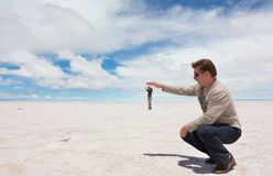 Funny photo because of spatial perspective. Spatial perspective on the lake Salar de Uyuni, Bolivia Stock Photos