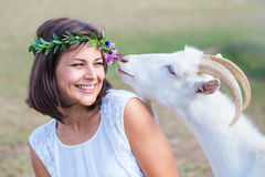 Funny picture a beautiful young girl farmer with a wreath on her. Head with white goat royalty free stock photos