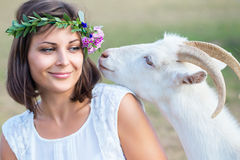 Funny picture a beautiful young girl farmer with a wreath on her. Head with white goat royalty free stock image