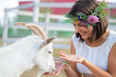 Funny picture a beautiful young girl farmer with a wreath on her. Head with white goat royalty free stock photography