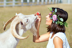 Funny picture a beautiful young girl farmer with a wreath on her. Head with white goat stock photo