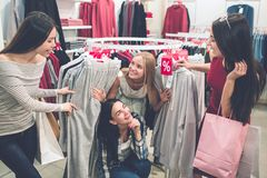 Funny picture of blonde and brunette girls are found under the round hanger and looking at their friends. They are. Smiling. Girls are having fun stock images