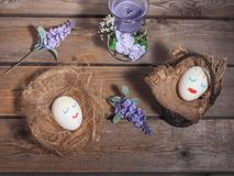 A funny picture for Easter, two eggs with painted faces. Basket and straw on which eggs sleep. Next sprigs of flowers on a wooden background stock images