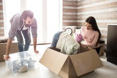 Funny picture of girl that is trying to find something in the box. Her parent are working besides her and laughing from. The situation. Father is holding box of Royalty Free Stock Images
