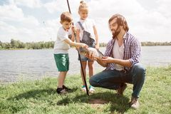 Funny picture of kids standing behind their father and looking at fish. They are amazed. Boy is holding fish-rod and. Touching fish. Guy is holding it and royalty free stock photo