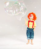 Funny picture of little clown making soap bubbles Stock Image