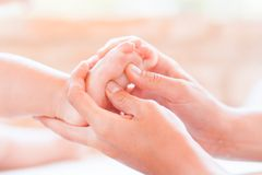 Funny picture of mothers hand and baby feet. Royalty Free Stock Photo