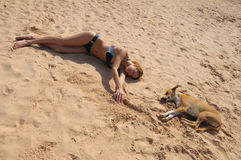 Funny picture of the same pose with girl and dog. The pretty girl is lying on the sand with the same pose as small red-white dog royalty free stock image