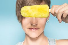 Funny picture of a woman eating ice cream. Girl covering her eyes with popsicle stock photos