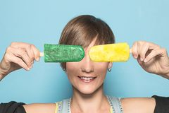Funny picture of a woman eating ice cream. Girl covering her eyes with popsicles stock photography