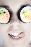 Funny picture of woman with sushi roll on her eye Stock Photo