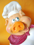 Funny pig with chef hat. Small curio, smiling pig with a chef hat over a yellow background Royalty Free Stock Images