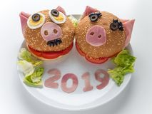 Funny piggies new year ham burgers, lettuce salad and 2019 digits on the plate. Funny piggies couple burgers, lettuce salad and 2019 digits made of the pork ham stock images