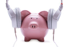 Funny piggy bank listening to stereo headphones Royalty Free Stock Photography