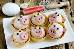 Funny pigs shaped snack tartlets. Stuffed with rice, surimi crab sticks, garlic and mayonnaise appetizer decorated with sausage stock photography