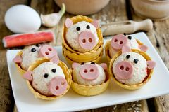 Funny pigs shaped snack tartlets stuffed with rice, surimi crab sticks, garlic and mayonnaise. Appetizer decorated with sausage royalty free stock images