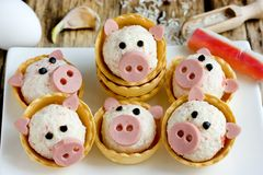 Funny pigs shaped snack tartlets stuffed with rice, surimi crab sticks, garlic and mayonnaise. Appetizer decorated with sausage stock images