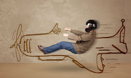 Funny pilot driving a hand drawn airplane on the wall Stock Photography