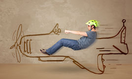Funny pilot driving a hand drawn airplane on the wall Stock Photo