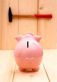 Funny pink piggy bank in focus and hammer on wood Royalty Free Stock Image