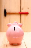 Funny pink piggy bank and hammer in focus on wood Royalty Free Stock Images