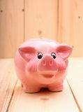 Funny pink piggy bank on wood background Royalty Free Stock Images