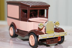 Funny pink vintage toy car. Macro of a funny pink vintage toy car with brown details and chrome front grille stock image