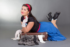 Funny pinup girl lying on overfilled suitcase Stock Image