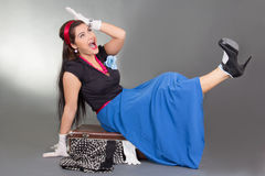 Funny pinup girl sitting on overfilled suitcase Stock Photos