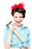 Funny pinup woman holding hammer. Funny beautiful pinup woman holding hammer isolated on white background stock photo