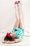 Funny pinup woman posing nicely legs up. Funny young blond pinup woman posing nicely over white background royalty free stock photo