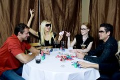 Funny players. Group of two couples having fun at a poker party, enjoying a drink Royalty Free Stock Images