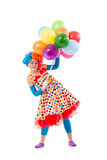 Funny playful clown. Funny playful female clown in colorful wig holding balloons, looking at camera and smiling, isolated on a white background Royalty Free Stock Photography