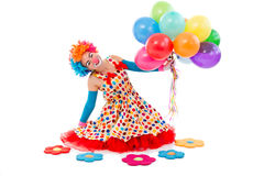 Funny playful clown. Funny playful female clown in colorful wig holding balloons, looking at camera and smiling, sitting near toy flowers isolated on a white Stock Photos